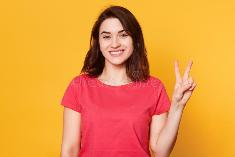 微笑的美丽的年轻女人穿戴了随便,显示两个手指或胜利姿态,被隔绝在黄色背景,有愉快 免版税库存图片