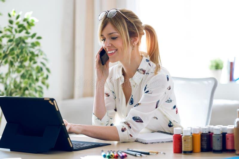 微笑的美丽的年轻设计师妇女与她的数字片剂一起使用,当谈话与她的手机在办公室时 库存照片