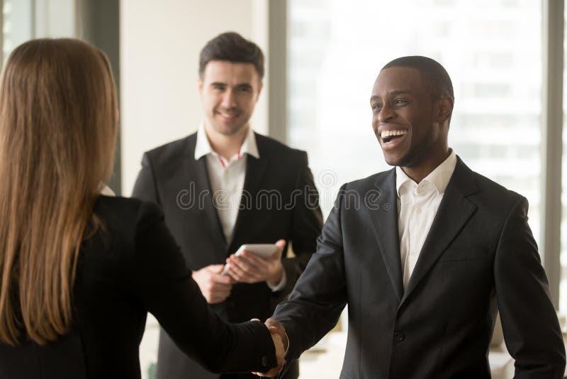 微笑的美国黑人的商人和白种人女实业家ha 免版税库存照片