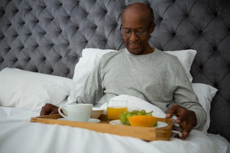 微笑的老人吃早餐在床上的盘子 库存照片