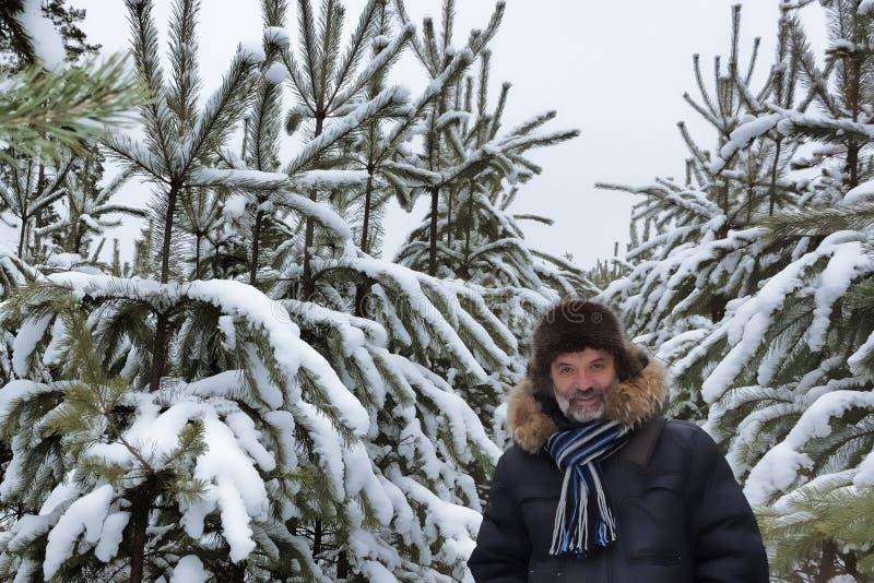 微笑的老人画象在一个积雪的冬天公园 库存照片