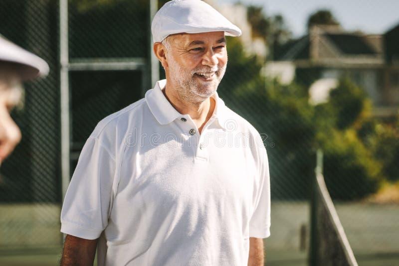 微笑的老人画象网球穿戴的 免版税库存照片