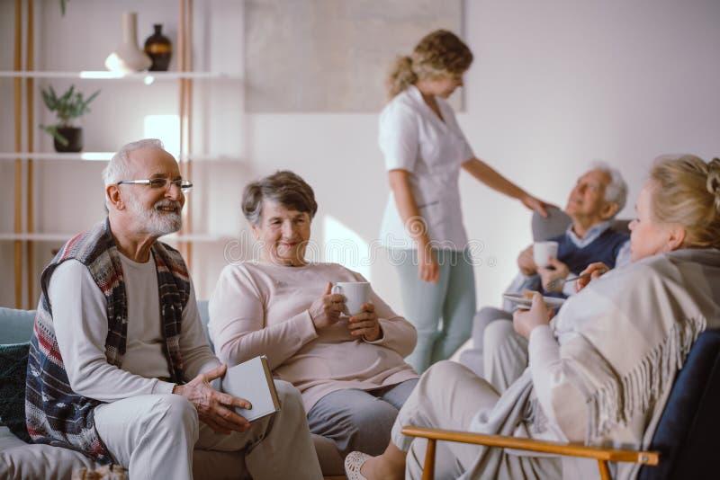 微笑的老人谈话与养老院的其他居民 免版税库存图片