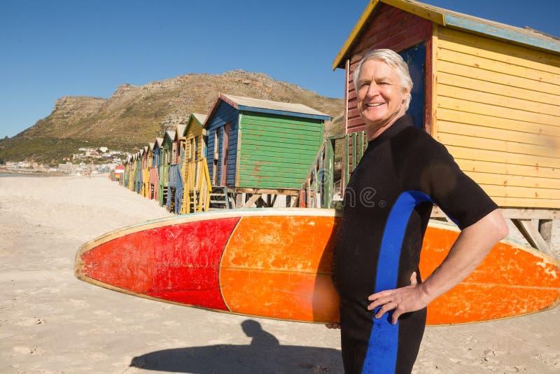 微笑的老人运载的冲浪板画象  免版税库存图片