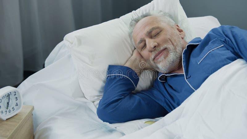 微笑的老人,当睡着早晨,在床上时的喜悦的领抚恤金者 免版税库存照片