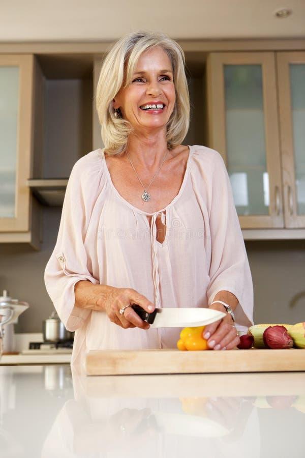 微笑的老妇人在切开新鲜蔬菜的厨房里 库存照片
