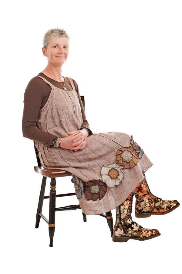 微笑的老妇人在开花的启动坐 免版税库存图片