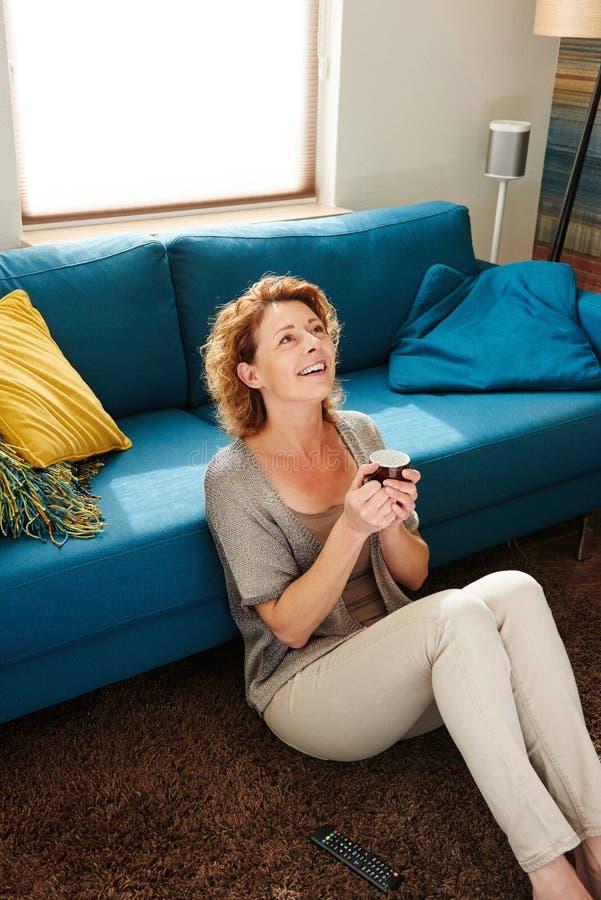 微笑的老妇人坐地板用热的咖啡 免版税库存照片