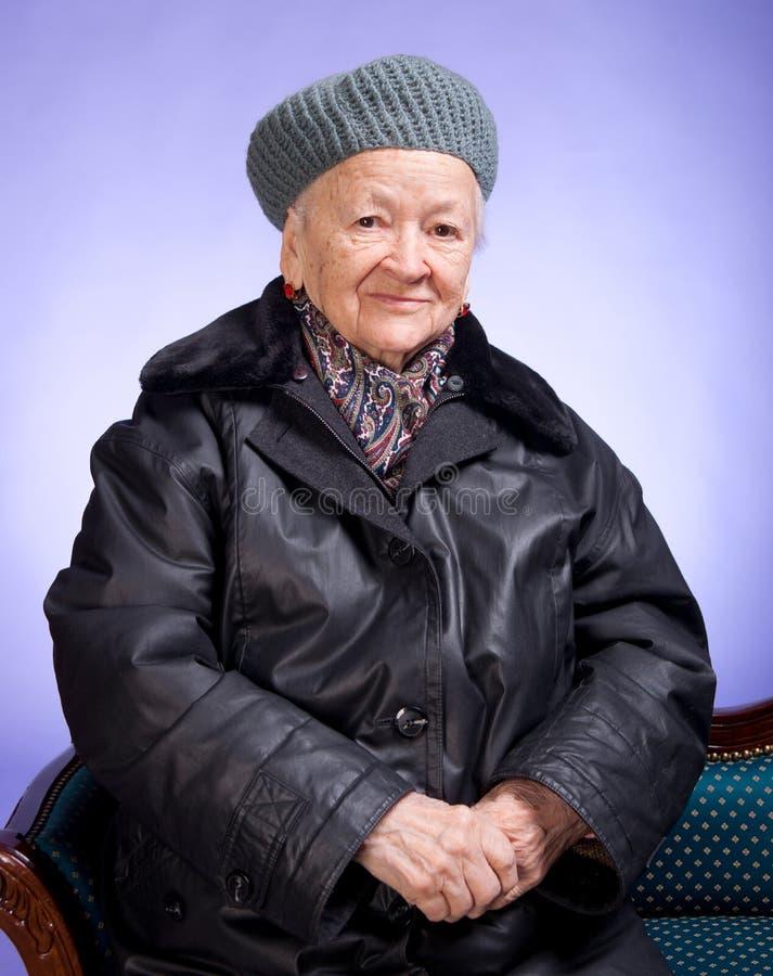 微笑的老妇人坐椅子 免版税库存图片