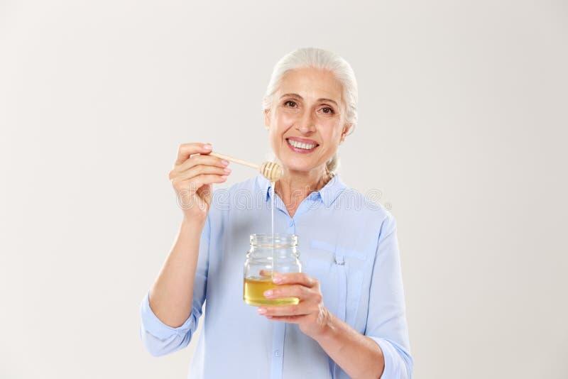 微笑的老妇人特写镜头画象,拿着有s的蜂蜜瓶子 免版税库存图片