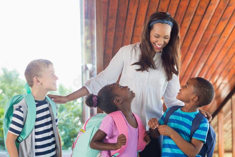 微笑的老师和孩子谈话互相 免版税库存图片