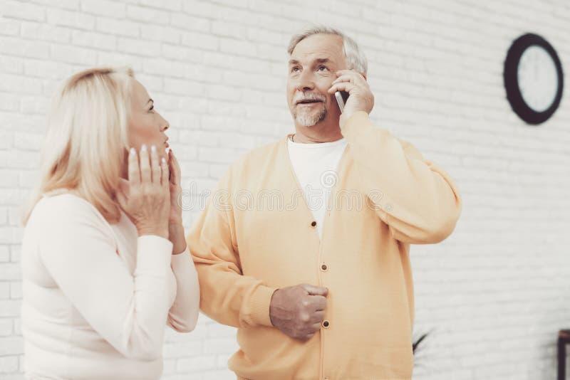 微笑的老男人和妇女谈话在智能手机 免版税图库摄影