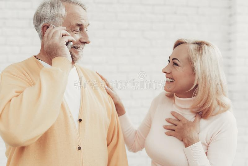 微笑的老男人和妇女谈话在智能手机 免版税库存图片
