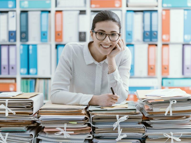 微笑的职员和堆文书工作 库存照片