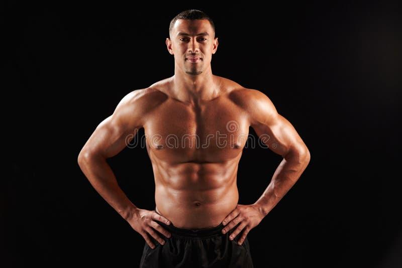 微笑的胸部赤裸的男性身体建造者用在臀部的手 库存图片
