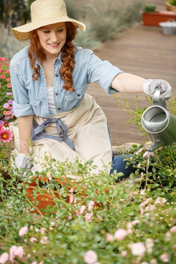 微笑的花匠妇女浇灌的花 免版税库存照片