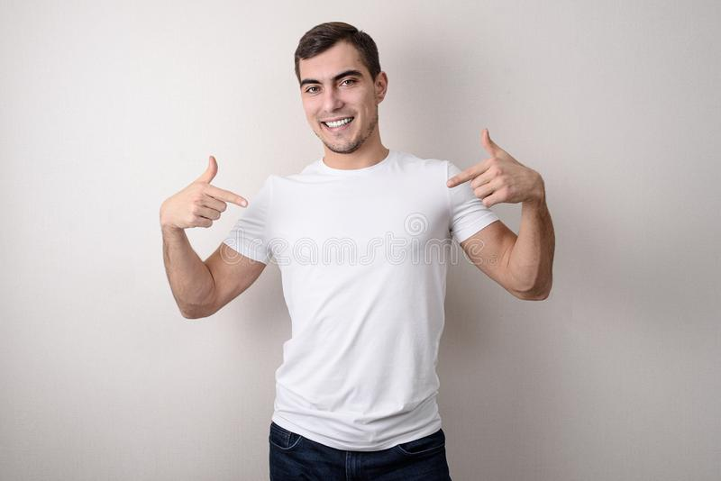 微笑的英俊的年轻人画象一件白色空白的T恤杉的显示她与他的手指,设计的地方 免版税库存图片