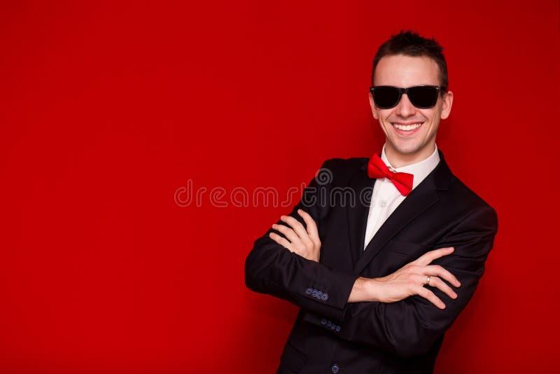 微笑的英俊的时髦的在红色背景的人和太阳镜画象典雅的黑衣服的 免版税库存图片