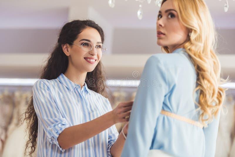 微笑的裁缝和客户在配件期间 图库摄影