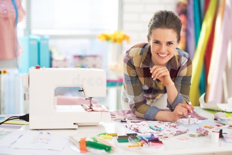 微笑的裁缝近的缝纫机画象  免版税库存照片