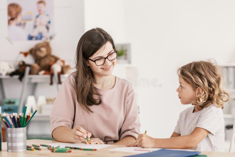 微笑的语言个别辅导工作与一个小男孩,画与c 图库摄影