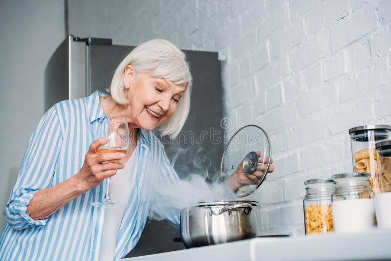 微笑的资深夫人侧视图有酒检查在火炉的杯的平底深锅 库存照片