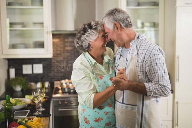 微笑的资深夫妇跳舞在厨房里 库存图片