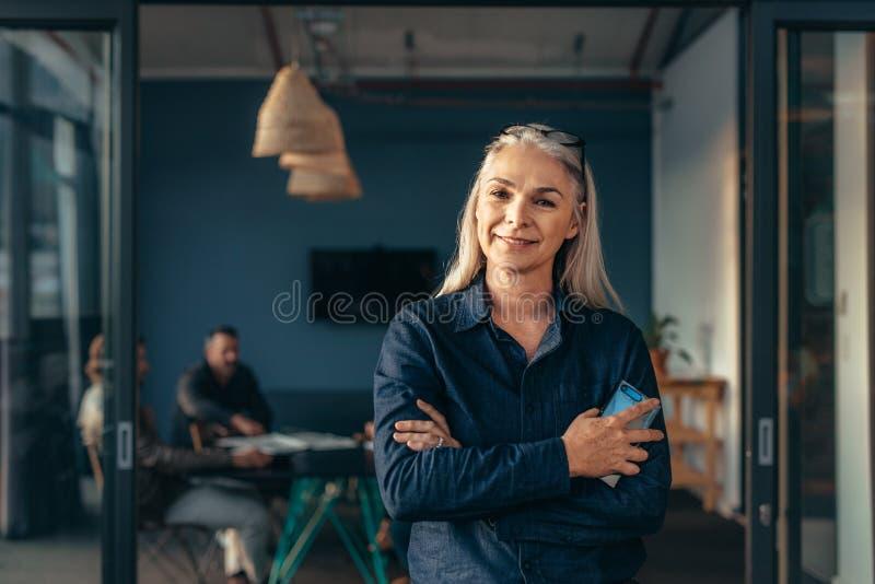 微笑的资深女商人在办公室 免版税库存照片