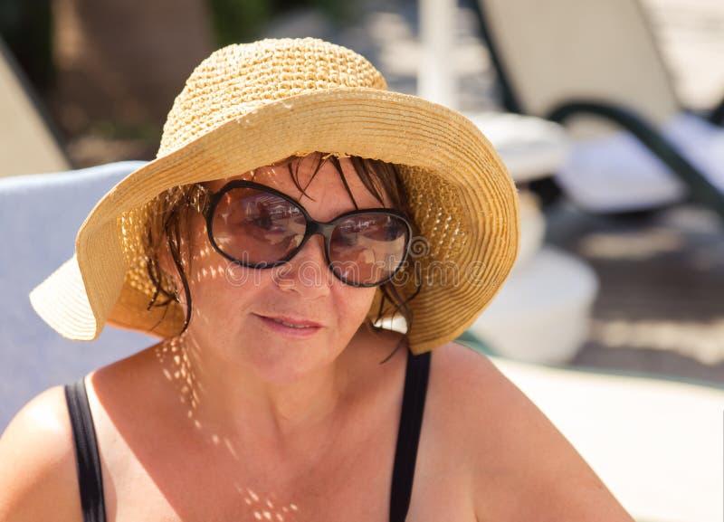 微笑的资深妇女佩带的帽子和太阳镜在海滩 免版税库存图片