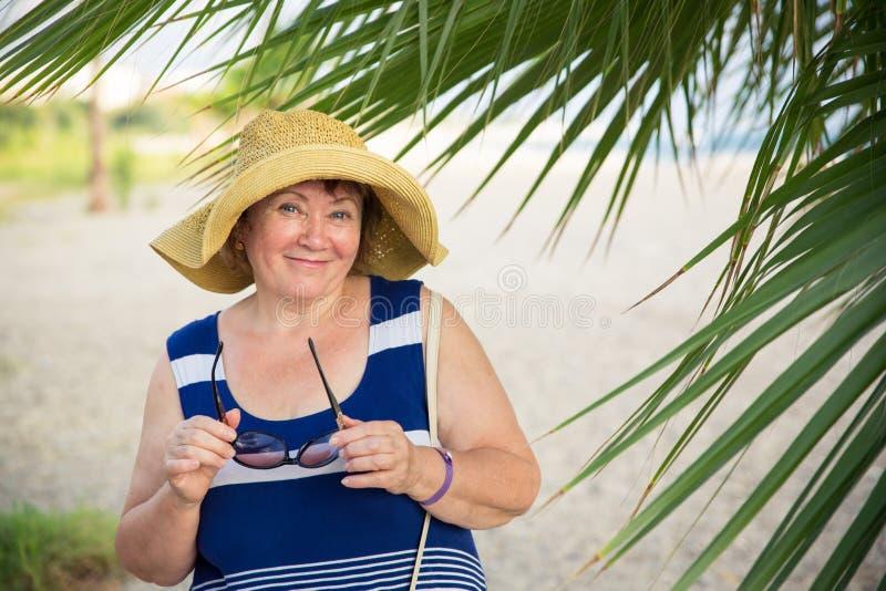 微笑的资深妇女佩带的帽子在棕榈树下 图库摄影
