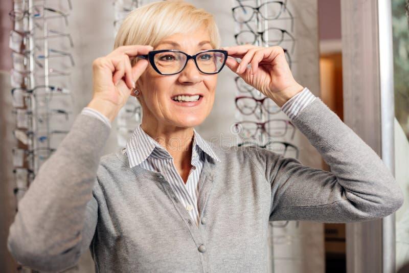 微笑的资深妇女尝试的处方玻璃在眼镜师商店 免版税库存照片