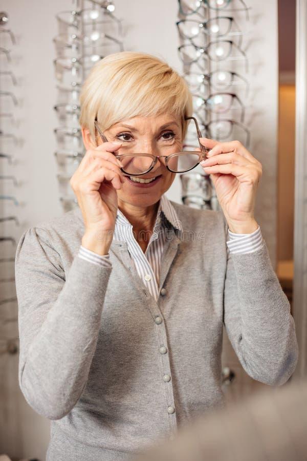 微笑的资深妇女尝试的处方玻璃在眼镜师商店 免版税图库摄影