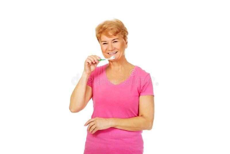 微笑的资深妇女掠过的牙 免版税库存照片