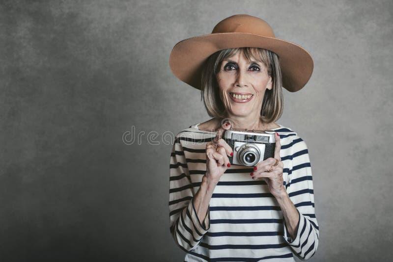 微笑的资深妇女画象有葡萄酒照片照相机的 免版税库存图片