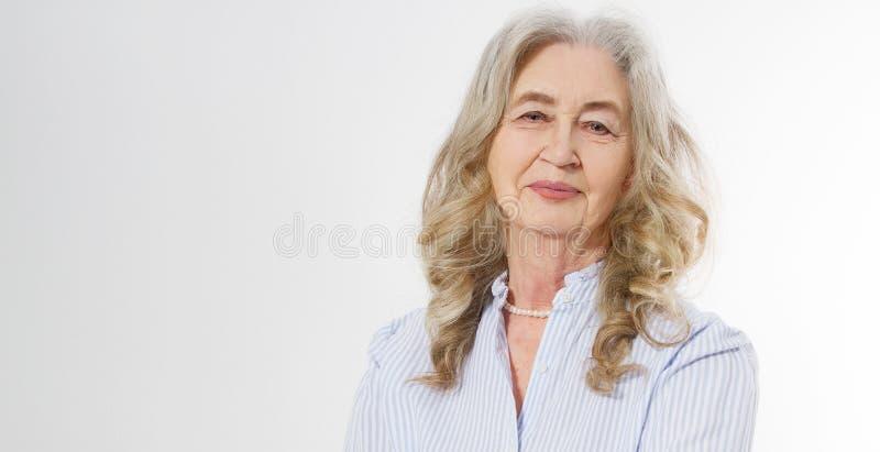 微笑的资深妇女皱痕面孔和灰色头发特写镜头  接触她的起皱纹的皮肤的老成熟夫人隔绝在白色 免版税库存图片