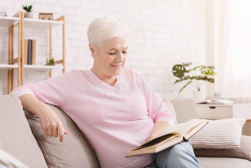微笑的资深妇女看书在家 免版税库存照片