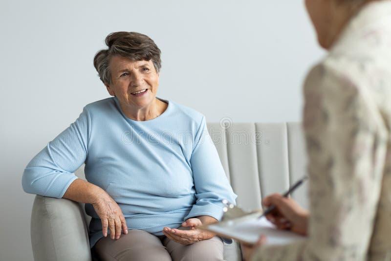 微笑的资深妇女谈话与一位心理学家关于愉快的生活 图库摄影