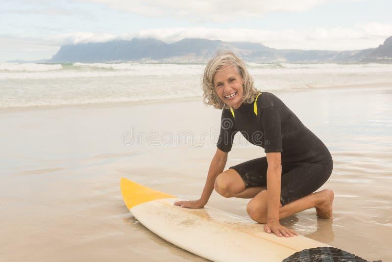 微笑的资深妇女画象为surfboarding做准备 库存图片