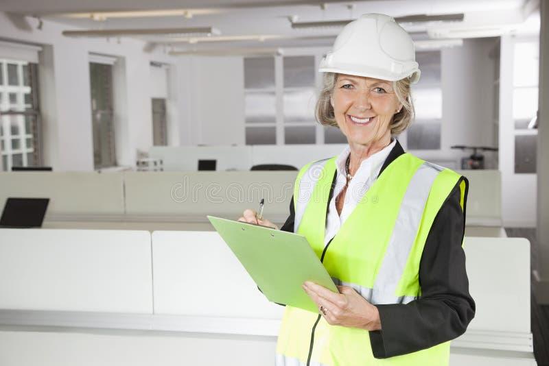 微笑的资深妇女画象拿着剪贴板的反射器背心和安全帽的在办公室 免版税图库摄影
