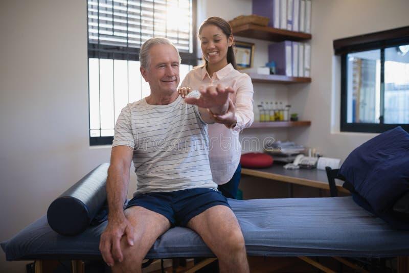 微笑的资深男性的患者和看起来女性的医生手头 库存照片