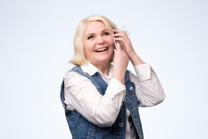 微笑的资深白肤金发的妇女谈话在电话 库存照片