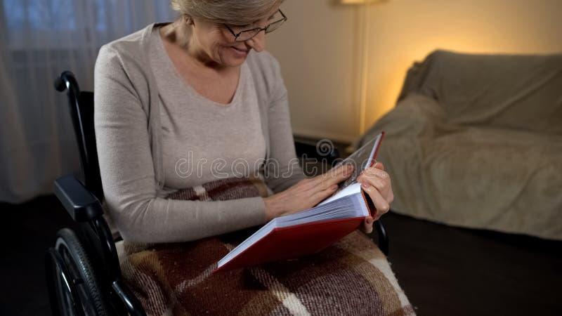 微笑的轮椅的夫人看在册页的照片和,好记忆 免版税库存图片
