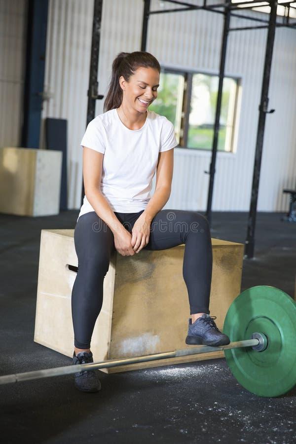 微笑的运动员坐箱子由在健身俱乐部的杠铃 免版税库存照片