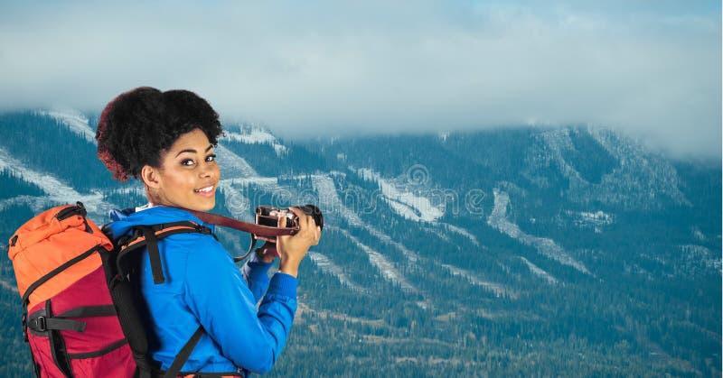 微笑的远足者画象有站立反对山的照相机的 免版税库存图片