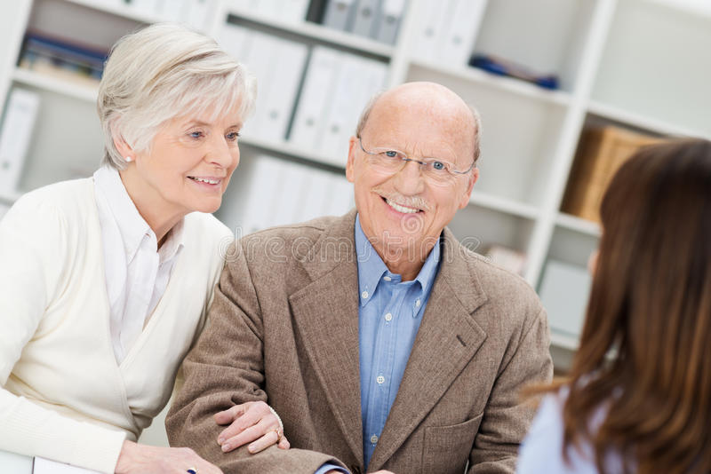 微笑的退休的夫妇在业务会议 免版税库存照片