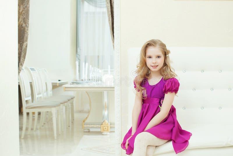 微笑的逗人喜爱的女孩的图象巧妙的紫色礼服的 免版税库存图片