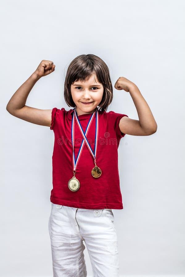 微笑的逗人喜爱的女孩自豪感摆在以自豪感和刺激 免版税库存照片