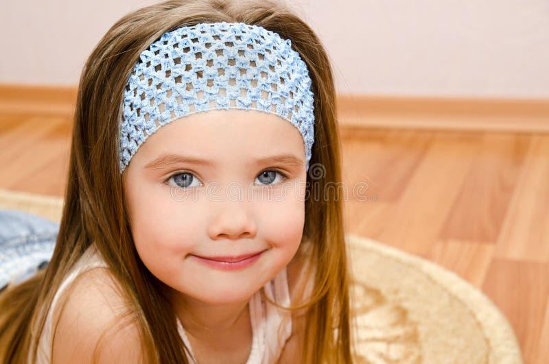 微笑的小女孩在房子地板上说谎 免版税图库摄影