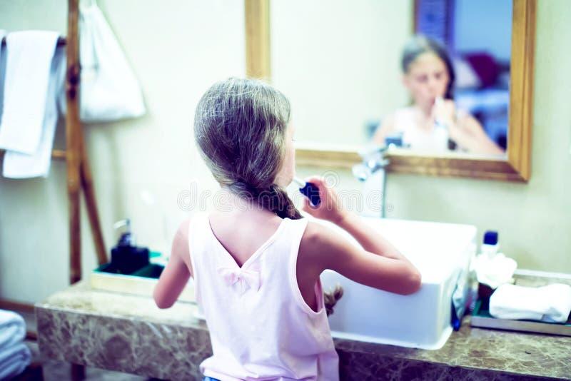 微笑的逗人喜爱的小女孩掠过的牙在卫生间里 卫生学骗局 免版税图库摄影
