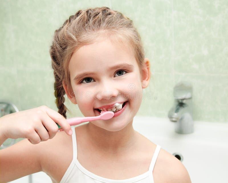 微笑的逗人喜爱的小女孩掠过的牙在卫生间里 免版税库存照片